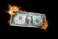 Burning money. A one dollar bill in American US currency is on fire Stock Photo