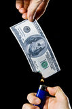 Burning Money. Putting fire to a us banknote on black background Royalty Free Stock Photo