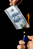 Burning Money. Putting fire to a us banknote on black background Royalty Free Stock Photos