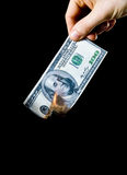 Burning Money. Putting fire to a us banknote on black background Stock Photos