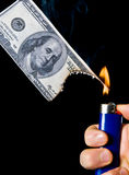 Burning Money. Putting fire to a us banknote on black background Royalty Free Stock Photography