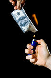 Burning Money. Putting fire to a us banknote on black background Stock Photo