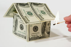 Burning money house made from dollars Stock Photo