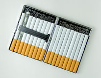 Burning Money. Pack of cigarettes - one of them is an actual dollar Royalty Free Stock Photography