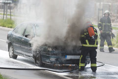 Burning motor vehicle been put out by firemen in protective clot Stock Photo
