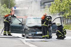 Burning motor vehicle been put out by firemen in protective clot Stock Photos