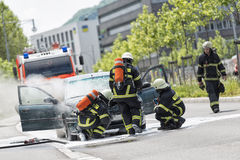 Burning motor vehicle been put out by firemen in protective clot Stock Image