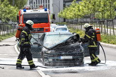 Burning motor vehicle been put out by firemen in protective clot Royalty Free Stock Image