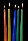 Burning of multi-colored candles on black Royalty Free Stock Photos