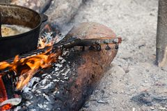 Burning neck of guitar and old sooty cauldron on campfire. At forest stock photo