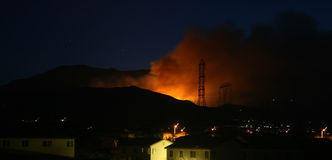 Burning through the night. Hillside fire comes frightening close to residential neighborhood Royalty Free Stock Image