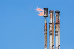 Burning oil flare. On a blue sky Royalty Free Stock Images