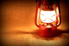 Burning oil lamp on burlap. Vintage concept Stock Photos