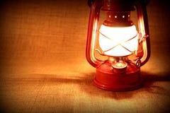 Burning oil lamp on burlap. Vintage concept Stock Photos
