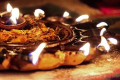 Diwali oil lamp with flames and dried flower petals royalty free stock photo