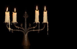 Burning old candle vintage bronze candlestick. Isolated Black Background. Stock Photography