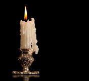 Burning old candle vintage bronze Silver candlestick. Isolated Black Background. Stock Photos