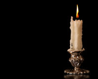 Burning old candle vintage Silver bronze candlestick. Black Background. Burning old candle vintage bronze candlestick. On Black Background royalty free stock photos