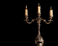 Burning old candle vintage Silver bronze candlestick. Isolated Black Background. royalty free stock image