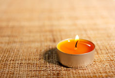 Burning orange candle placed on jute material Stock Images