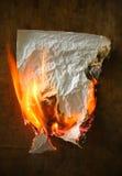 Burning paper. On dark wood background royalty free stock photography