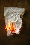 Burning paper. On dark wood background stock photos