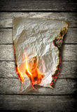 Burning paper. On wood background stock images