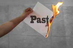 Burning past word text with fire on paper. In hand stock photo