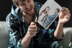 Burning photo with ex-girlfriend. Angry young men burning photo with ex-girlfriend Royalty Free Stock Image