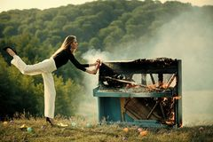 Burning piano and fashion woman at rock concert. Firefighting of girl with extinguisher. Music style and art. Fire and. Smoke on grunge instrument. woman with royalty free stock photos
