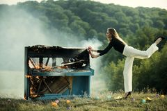 Burning piano and fashion woman at rock concert. Firefighting of girl with extinguisher. Music style and art. Fire and. Smoke on grunge instrument. woman with royalty free stock images