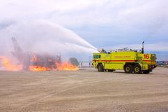 Burning Plane. A yellow fire truck spraying with foam a mock-up plane during an open house fire drill Royalty Free Stock Photos
