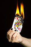 Burning the queen of diamonds Royalty Free Stock Image