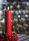 Burning Red Candle. A tall burning red candle with berry wreath and lights from Christmas tree blurred in background Stock Photography