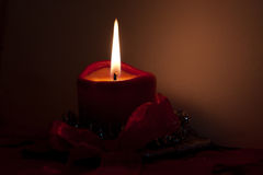 Burning red candle. Closeup of single burning red candle with dark background stock illustration