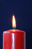 Burning red candle. A closeup of the orange flame burning on a candle against a dark background Stock Image