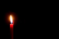 Burning red candle with black background Stock Images