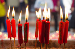 Burning red candle at chinese shrine for making merit in chinese Royalty Free Stock Image