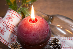 Burning red candle with glass and pine cone decorated Stock Photography