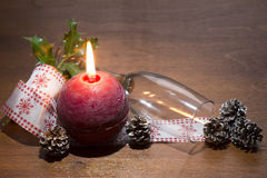 Burning red candle with glass and pine cone decorated Stock Photos