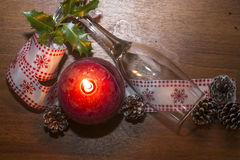 Burning red candle with glass and pine cone decorated Stock Image