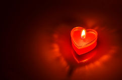 Burning red candle heart Stock Images