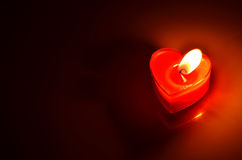 Burning red candle heart. Close Up of burning red candle heart on dark background Stock Image