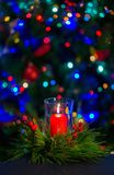 A burning red candle in the middle of the Christmas wreath against the dark background on the christmas tree stock photo