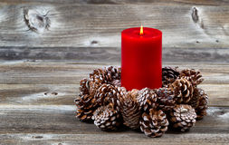Burning Red Candle and Pine Cone Wreath for Christmas Season Stock Photo