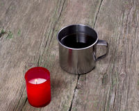 The burning red candle and steel cup of coffee Royalty Free Stock Images