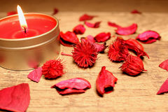 Burning red candle on the table. With petals and flowers Stock Photos