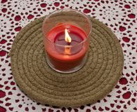 A burning red candle on a table with a white and red cloth. A red candle in a glass jar on a green cloth plate sitting upon a white and red table cloth Stock Image