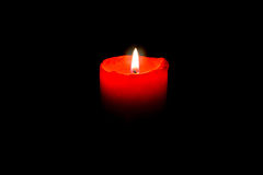 Burning red candle in total darkness Royalty Free Stock Photos