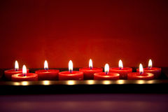 Burning red candles. And red background royalty free stock photo